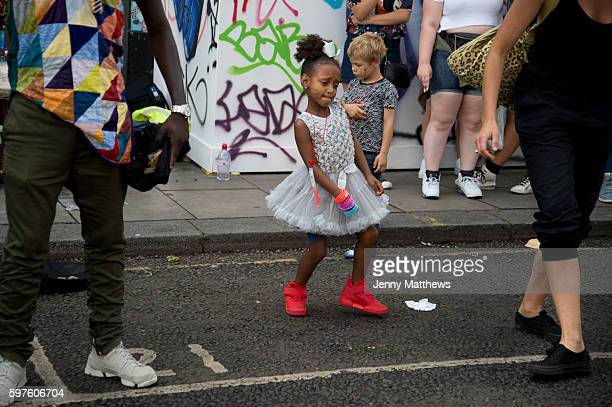 Notting Hill Carnival 2016 Children's Day A little girl wearing a white party dress and red trainers dances in the street to a busking band