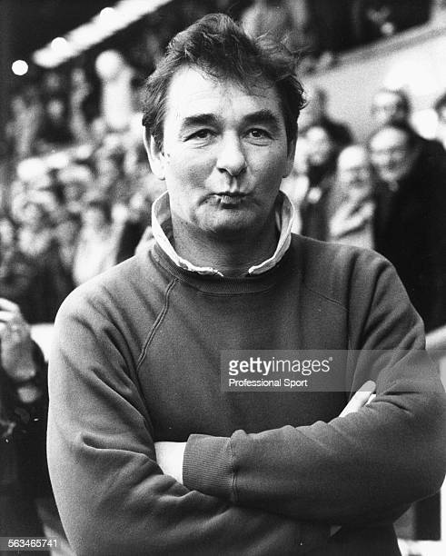 Nottingham Forest Football Club manager Brian Clough stands beside the pitch with his arms folded, circa 1984.