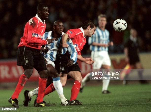 Nottingham Forest's Chris BartWilliams and Andy Johnson squeeze out Huddersfield Town's Michel Ngonge