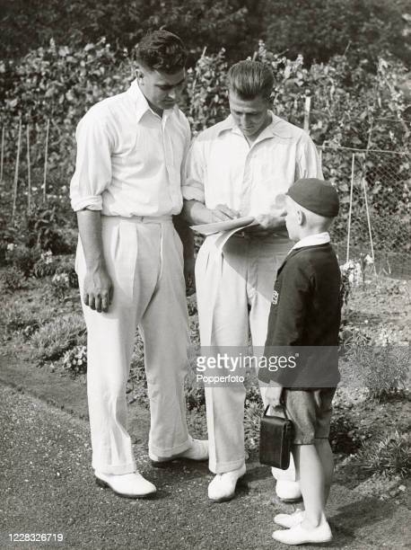 Nottinghamshire and England cricketers Bill Voce and Harold Larwood signing autographs for a schoolboy, circa 1935.
