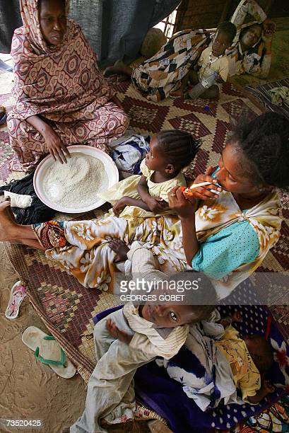 TO GO WITH AFP FRENCH STORY BY CHRISTOPHE PARAYRE A family prepare their meal 07 March 2007 inside their shack made of corrugated iron and wood in a...