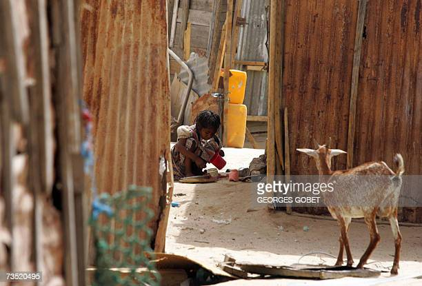 TO GO WITH AFP FRENCH STORY BY CHRISTOPHE PARAYRE A Mauritanian girl washes her family's kitchen utensils 07 March 2007 outside their shack made of...