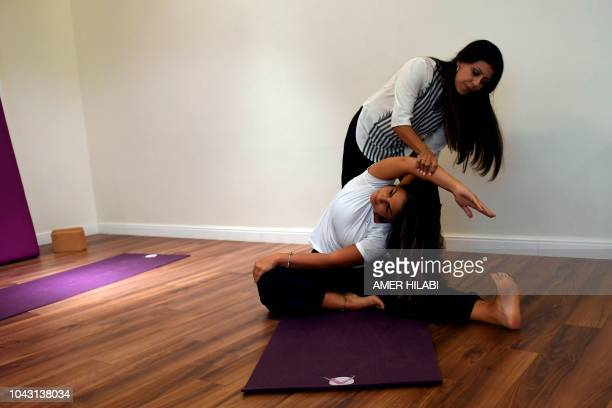 Nouf Marwaai the head of the Arab Yoga Foundation helps Budur alHamoud with a yoga pose at her studio in the western Saudi Arabian city of Jeddah on...