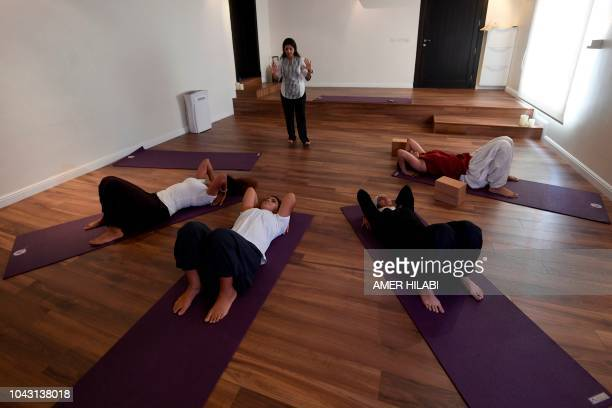 Nouf Marwaai the head of the Arab Yoga Foundation instructs a yoga class at her studio in the western Saudi Arabian city of Jeddah on September 7...
