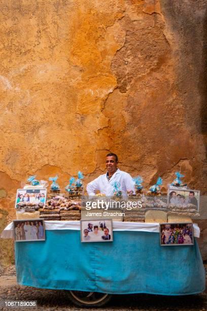 nougat seller behind his mobile cart with pictures of moroccan royal family, kasbah des oudaias, unesco world heritage site, rabat, morocco (model release) - cultura marroquí fotografías e imágenes de stock