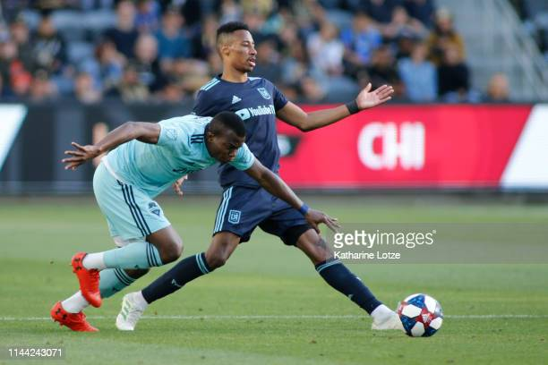 Nouhou Tolo of Seattle Sounders and MarkAnthony Kaye of Los Angeles FC fight for control of the ball during a game at Banc of California Stadium on...
