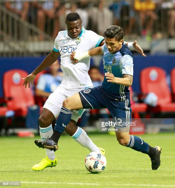 Nouhou Tolo of the Seattle Sounders battles with Fredy Montero of the Vancouver Whitecaps FC as he dribbles the ball up field during their MLS game...