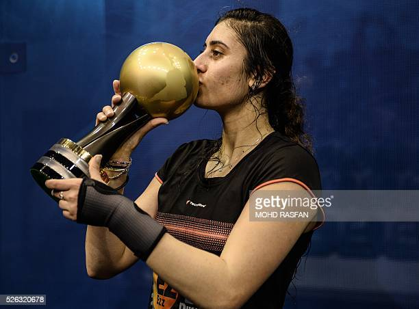 Nour El Sherbini of Egypt kisses her trophy after winning against Laura Massaro of England after their final match of the PSA Women's World...