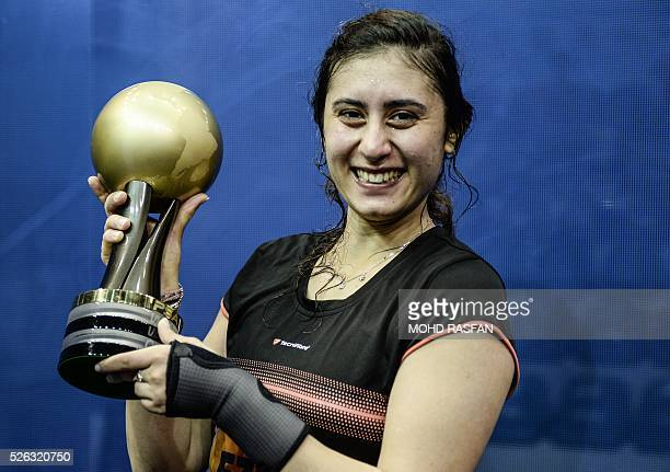 Nour El Sherbini of Egypt poses with her trophy after winning against Laura Massaro of England after their final match of the PSA Women's World...