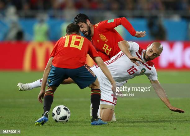 Noureddine Amrabat of Morocco is challenged by Jordi Alba of Spain and Isco of Spain during the 2018 FIFA World Cup Russia group B match between...