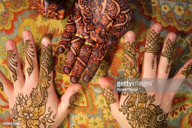 Noureen Sultana's hand top adorned with finished henna and the hands of Amy Vulfovich displaying freshly applied henna An esteemed artist in her...