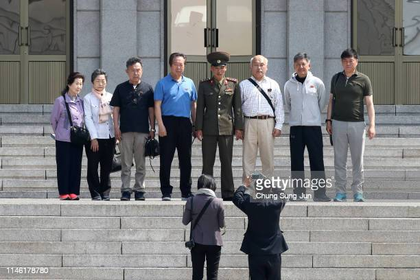 Nouth Korean visitors pose for photographs with a North Korean soldier as they tour the North Korean side of the truce village of Panmunjom inside...