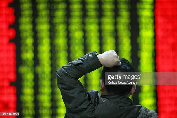 Nov. 13, 2015 -- An investor looks through stock information at a trading hall in a securities firm in Huaibei, east China's Anhui Province, Nov. 13,...