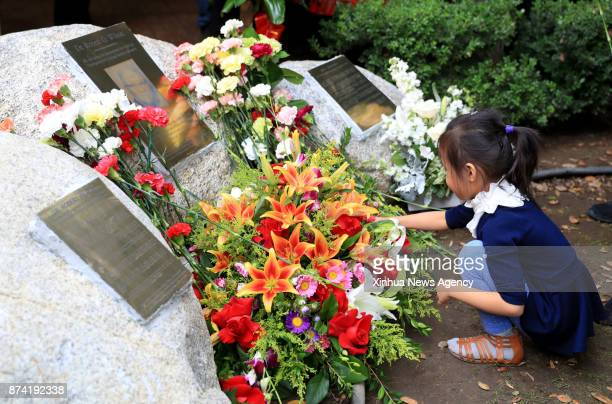 A girl presents flowers to Dr Robert Wilson's memorial tablet after its unveiling in Los Angeles the United States Nov 12 2017 Dr Robert Wilson an...