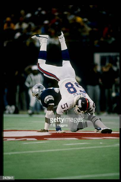 Linebacker Carl Banks of the New York Giants is blocked by running back Herschel Walker of the Dallas Cowboys during a game in Giants Stadium at the...