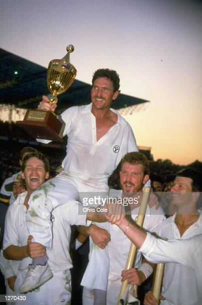 Allan Border of Australia is supported by his team mates as he holds the trophy aloft after the World Cup final against England at Eden Gardens in...