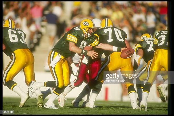 Quarterback Anthony Dilweg of the Green Bay Packers hands the ball off during a game against the Phoenix Cardinals at Sun Devil Stadium in Tempe...