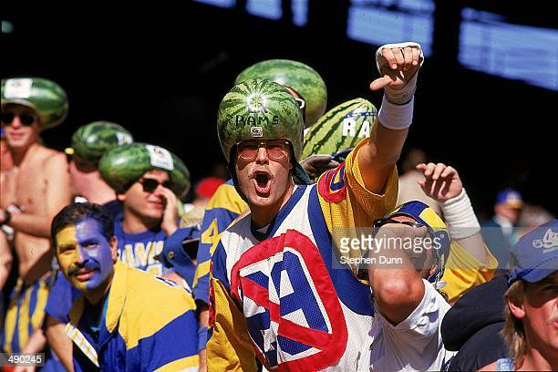 Fans wear watermelon on their heads as they cheer on the Los Angeles Rams during a game against the San Francisco 49ers at the Anaheim Stadium in...