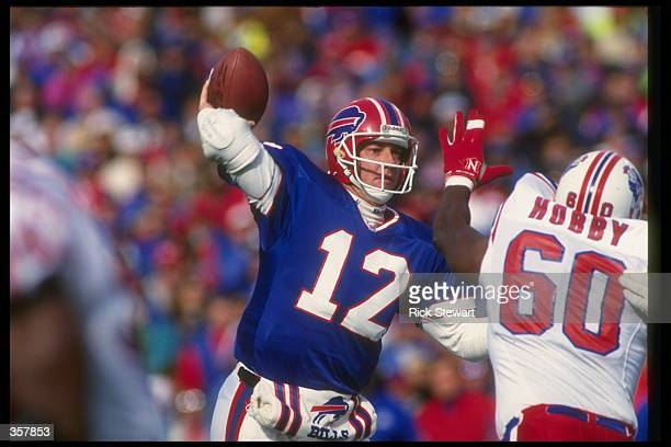 Quarterback Jim Kelly of the Buffalo Bills passes the ball during a game against the New England Patriots at Rich Stadium in Orchard Park New York...