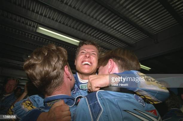Benetton Ford driver Michael Schumacher of Germany hugs two team mechanics in delight for becoming World Champion Driver after the Australian Grand...