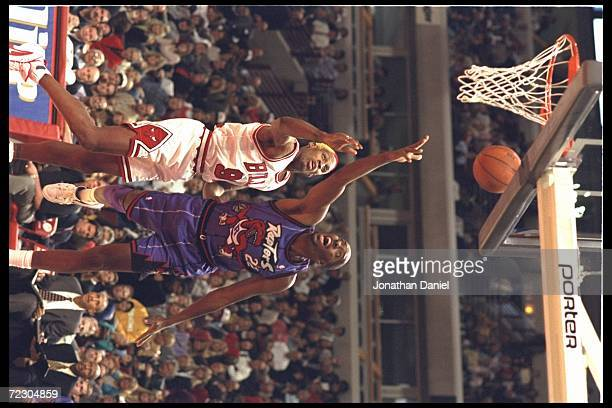 Center John Salley of the new expansion team Toronto Raptors and guard Dennis Rodman of the Chicago Bulls go up for the rebound at the United Center...