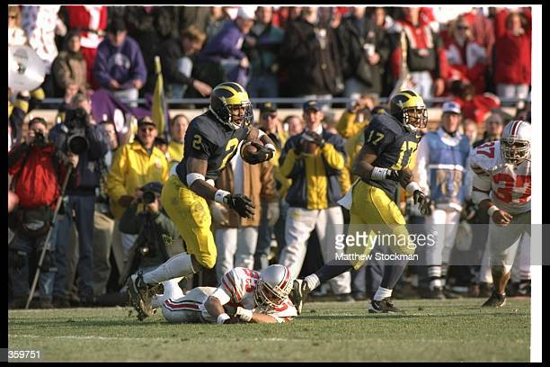 Defensive back Charles Woodson of the Michigan Wolverines runs with the ball after intercepting it during a game against the Ohio State Buckeyes at...