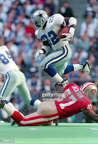 Emmitt Smith of the Dallas Cowboys with the ball jumps over Rickey Jackson of the San Francisco 49ers during the game at the Texas Stadium in Irving...
