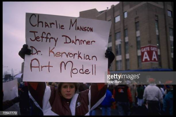 Fans hold various signs which accuse Cleveland Browns owner Art Modell of disregard of fans which compares him to famous murderers at Cleveland...