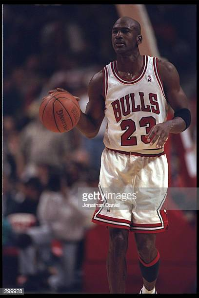 Guard Michael Jordan of the Chicago Bulls sizes up the Charlotte Hornets who are waiting for him at the other end of the court at the United Center...