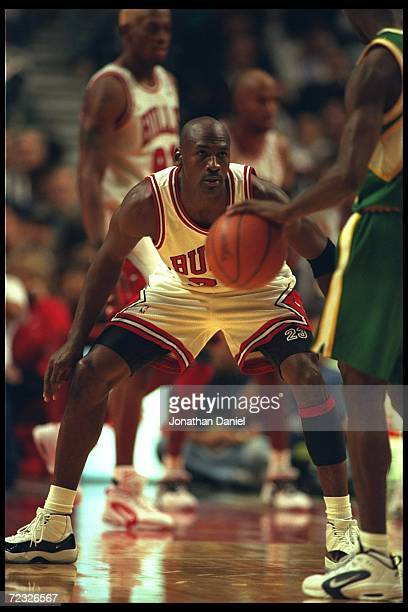 Guard Michael Jordan of the Chicago Bulls watches with intense concentration the moves of a Seattle Supersonic forward at the United Center in...