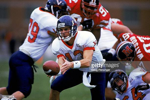 Mike Groh of the Virginia Cavaliers hands off the ball during a game against the Maryland Terrapins at the Byrd Stadium in College Park Maryland The...