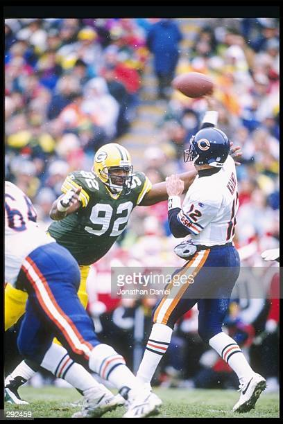 Quarterback Erik Kramer of the Chicago Bears passes the ball as defensive end Reggie White of the Green Bay Packers puts on the pressure at Lambeau...