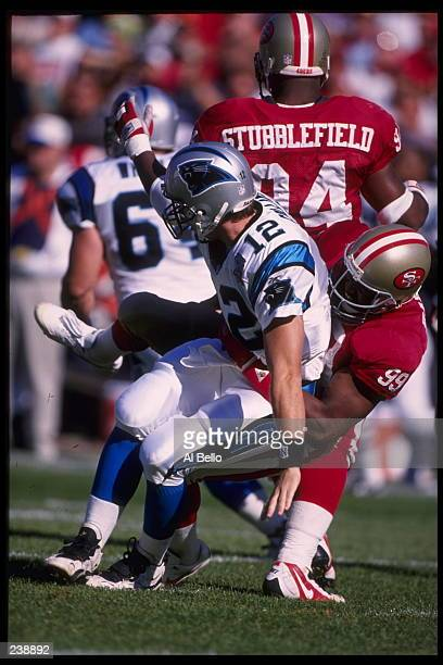 Quarterback Kerry Collins of the Carolina Panthers is brought down by defensive end Tim Harris of the San Francisco 49ers at 3COM Park in San...