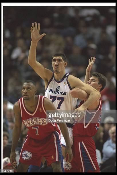 Center Gheorghe Muresan of the Washington Bullets and Philadelphia 76ers player Mark Bradtke look for the ball during a game at the USAir Arena in...