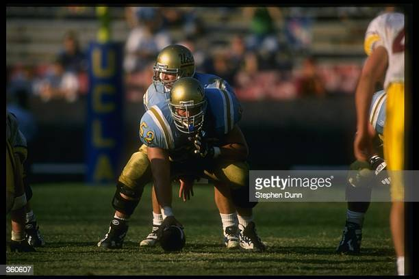 Center Shawn Stuart of the UCLA Bruins prepares to snap the ball to quarterback Cade McNown during a game against the USC Trojans at the Rose Bowl in...