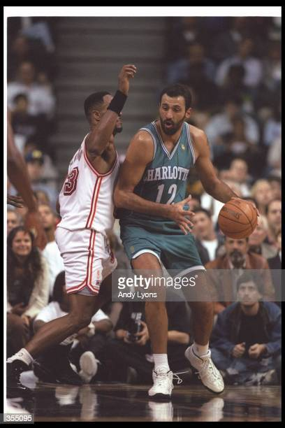 Center Vlade Divac of the Charlotte Hornets moves the ball as Miami Heat center Alonzo Mourning covers him during a game at the Miami Arena in Miami...