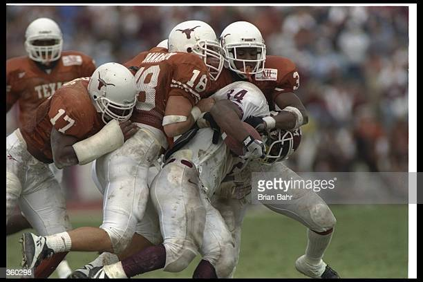 Dante Hall of the Texas A&M Aggies gets tackled by several Texas Longhorns players during a game at Texas Memorial Stadium in Austin, Texas. Texas...