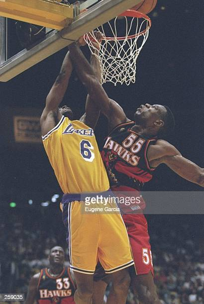 Guard Eddie Jones of the Los Angeles Lakers drives to the basket as center Dkembe Mutombo of the Atlanta Hawks tries to block him during a game at...