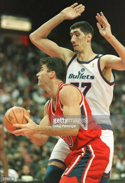 Guard Mark Bradtke of the Philadelphia 76ers tries to get past Georghe Muresan of the Washington Bullets as the Bullets posted a 48-35 halftime lead...