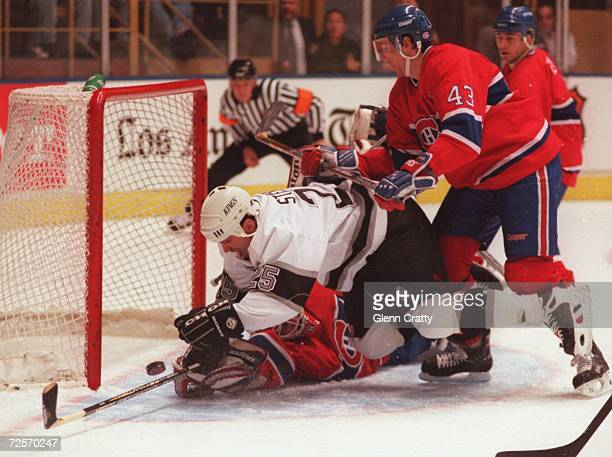 Kevin Stevens of the Kings puts a shot on net as he is knocked down by Patrice Brisebois of the Canadiens as goaltender Jose Theodore sprawls for the...