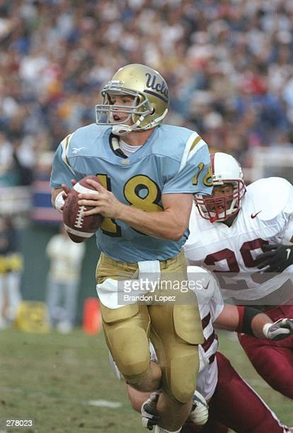 Quarterback Cade McNown of the UCLA Bruins looks down field for an open receiver as he scrammbles out of the pocket while being pressured by pursuing...