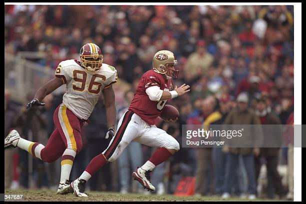 Quarterback Steve Young of the San Francisco 49ers moves the ball as Washington Redskins defensive lineman Rich Owens chases him during a game at RFK...