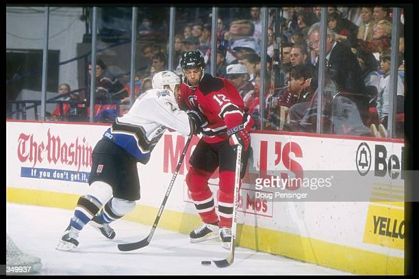 Rightwinger Bill Guerin of the New Jersey Devils and Washington Capitals defenseman Ken Klee tangle up during a game at the USAir Arena in Landover...