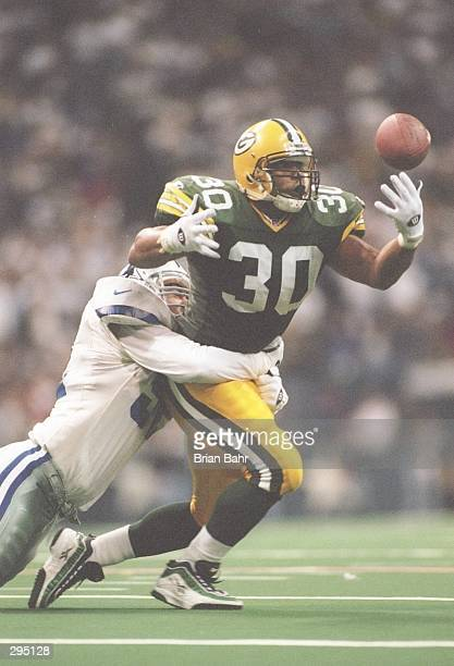 Running back William Henderson of the Green Bay Packers is wrapped up by linebacker Jim Schwantz of the Dallas Cowboys while making a hands out...