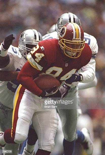 Tight end Jamie Asher of the Washington Redskins tries to break away from defenders during a game against the Dallas Cowboys at Texas Stadium in...