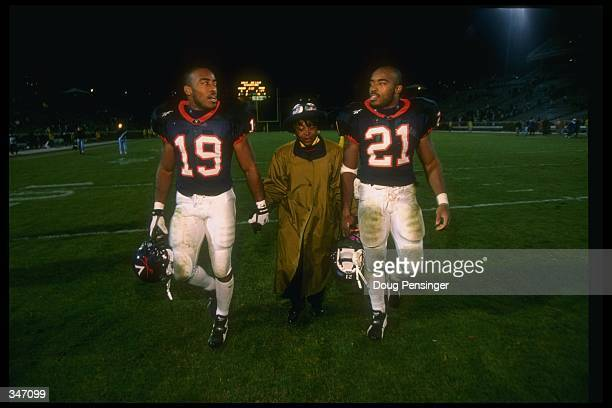 Virginia Cavaliers players and twin brothers running back Tiki Barber and cornerback Ronde Barber walk onto the field with their mother before a game...
