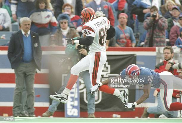 Wide receiver Carl Pickens of the Cincinnati Bengals jumps as defensive back Raymond Jackson of the Buffalo Bills tries to tackle him during a game...