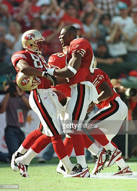 Wide receiver Iheanyi Uwaezuoke of the San Francisco 49ers is congratulated by teammate Terrell Owens after a touchdown reception against the Dallas...