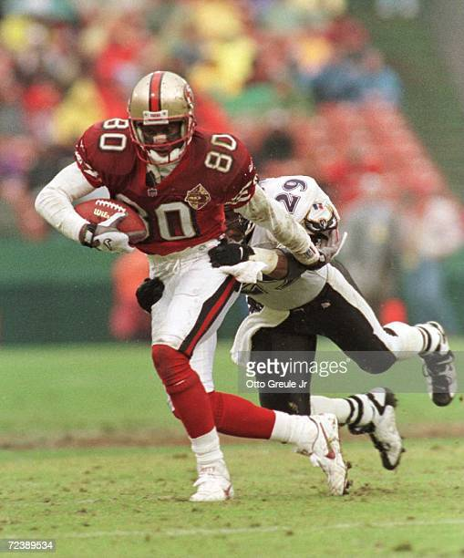 Wide receiver Jerry Rice of the San Francisco 49ers is wrapped up by safety Eric Turner of the Baltimore Ravens in the second half of the 49ers 3820...