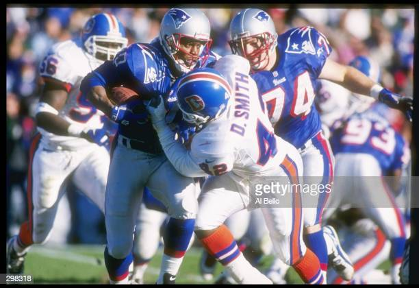 Wide receiver Troy Brown of the New England Patriots tries to break away from safety Dennis Smith of the Denver Broncos during a game at Foxboro...